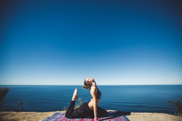 Person macht Yoga am Meer